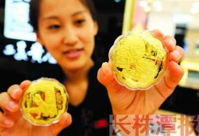 """北京一工作人员在展示一款中秋题材的""""黄金月饼""""产品。 图/新华社"""