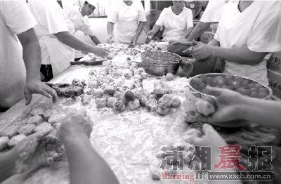 19日,巢娭毑月饼店,员工在徒手制作蛋黄月饼,没戴口罩。图/记者华剑