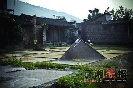 湖南永州,周家大院。午后,两位村民在黑门楼前晾晒稻谷。这里经济落后,交通不便。村民基本以自给自足的方式生存。