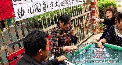 9月27日下午,长沙才子佳苑小区,居民堵着托儿所,在大门口打麻将,他们称托儿所制造噪音。 图/记者刘有志
