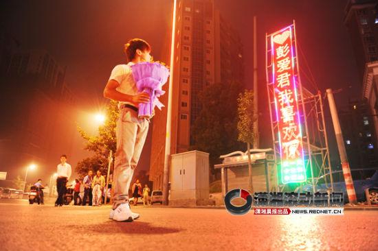 (9月27日晚,长沙金盆岭一路口,25岁小伙自制霓虹灯向网友示爱。图/潇湘晨报滚动新闻记者 李坤)
