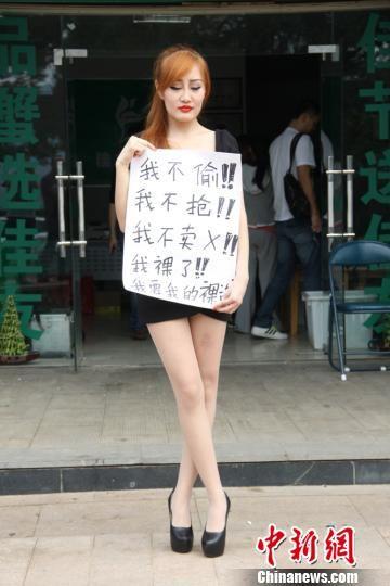 """性感女子大闸蟹店门外举""""我要我的裸资""""牌子,向店主讨要""""裸资""""。 刘柱 摄"""