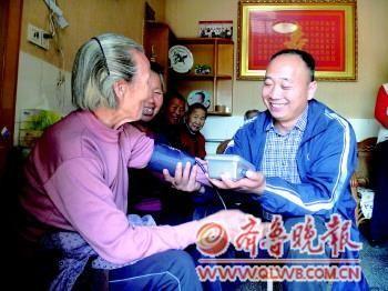 孙连祥给村里老人量血压。 本报记者 李沙娜 摄