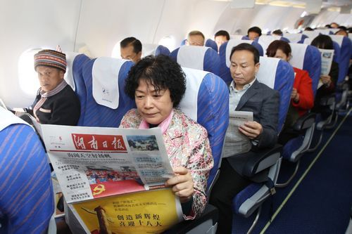 11月6日,出席党的十八大的湖南代表,在赴京参会的飞机上阅读当天的《湖南日报》。本报记者 罗新国 张 目 摄