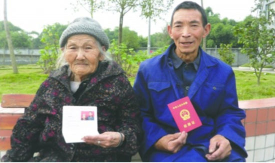 张玉良、贺吉珍两位老人手持结婚证合影留念