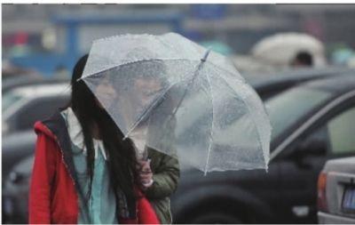 11月9日,长沙火车站前广场。濛濛冬雨中,两个美女撑着透明雨伞迎风前进。 记者 李丹 摄