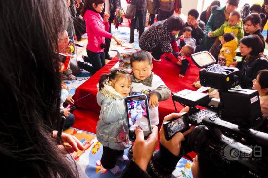 2012年11月11日上午,湘春路金地大厦22楼 ,BB团宝宝相亲会,俩岁半的朵朵和乐乐在游戏中配对成功,他们开心的在一起拍合影。图 活动方提供