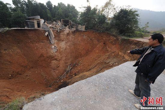 """11月19日,湖南长沙岳麓区雨敞坪镇泉宏村的一栋两层楼房已被塌陷的坑洞""""吞噬""""。据泉宏村村民介绍,16日凌晨正值雨夜,当地村民发现了地面塌陷形成的大坑,坑洞且不断蔓延扩大。一天后,坑洞已将两层楼房""""吞噬""""。大坑面积约200平方米、深约30米,坑洞边留下房子的残骸。中新社发 杨华峰 摄"""