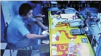 11月19日,长沙市曙光北路,视频截图显示,学徒小胡正从抽屉里拿钱。 实习生 李健 摄