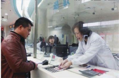11月30日上午,湘雅医院,参合农民朱先生正在结算窗口领取报销退款。 通讯员 武海亮 摄