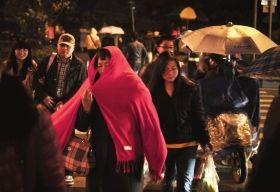 12月9日,中南大学铁道学院公交车站台附近,一位市民用红色围巾包裹头部,抵御寒风。图/记者辜鹏博