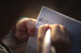 12月7日,衡阳市某村,小月在外公家里,把妈妈的电话记到本子上。图/记者李坤