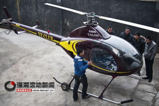 (长沙宁乡县人小王正在检查重新上色后的直升机,这架直升机价值180万元。图/潇湘晨报滚动新闻实习生 蒋丽梅)
