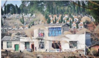 12月23日,湘潭市九华经济开发区狮山村叶塘组,村民的房屋被一排排整齐的墓碑包围。 记者 范远志 摄