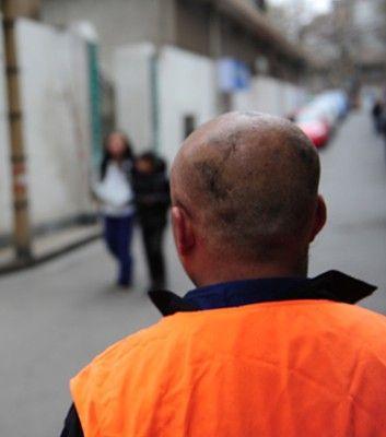"""公厕值班的老侯一觉醒来发现头发没了,他现在很不习惯自己的""""新发型""""。图/记者辜鹏博"""