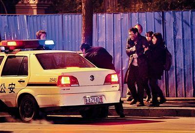 暗访记者戴鹏(中间戴眼镜者)被警察和好心市民接走前往救助站