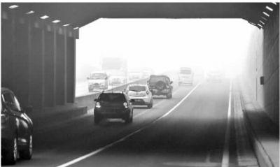 1月13日早晨,雾气弥漫,长沙市湘江北路浏阳河隧道南出口,路上的机动车都开着警示灯前行。记者 田超 摄