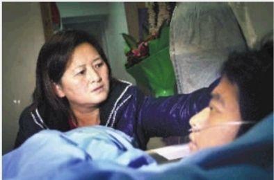 """▲1月17日,湘雅二医院,符小红轻抚儿子头发,说""""一切都会好起来的,我还等着你兑现承诺。"""" 实习生 李健 摄"""