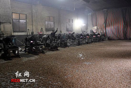 (工作人员将生产出来的爆米花直接洒在坑坑洼洼、布满灰尘的地板上。)