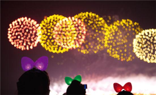 2012年7月21日,长沙市杜甫江阁附近,炫目的焰火和女孩头上的蝴蝶结在夜晚交相辉映。图/记者沈荣华