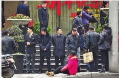 2月19日,长沙市八一路富丽华酒店,死者家属伤心地坐在酒店门前。 记者 童迪 摄