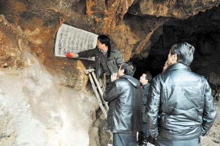 """专家在洞口右侧石壁上发现石碑刻文,""""大酉洞天""""几个字依稀可辨。 资料图片"""