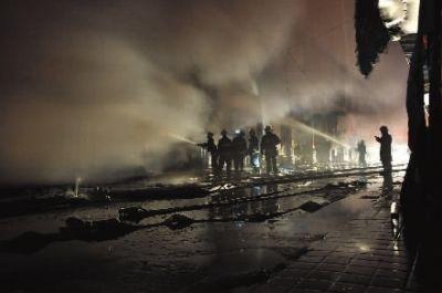 晚9时许,火势减弱,消防队员在跟火苗做最后的斗争。实习记者 唐俊 摄