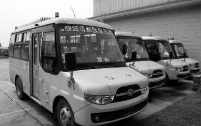 """3月15日下午,四家幼儿园将""""多病""""的新校车停放在一起,等待检测及厂方回复。记者 徐德荣 摄"""