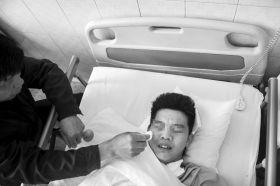 4月7日,宁乡县人民医院,小曾的爸爸拿着纸巾默默地给儿子擦泪。图/实习记者杨旭