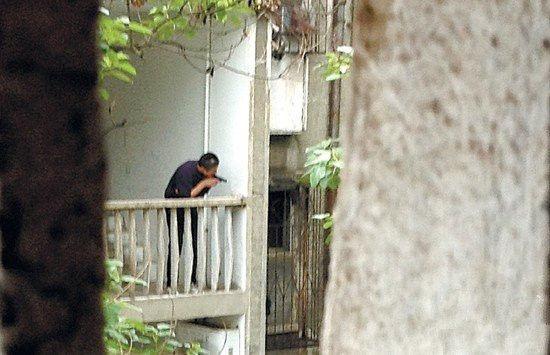 5月9日,持枪男子在车站北路朝阳一村25栋5楼与楼下警方对峙,随后躲入民居。