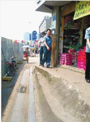 """长沙市雨花亭小学校门附近,一栋私房将人行横道截断,剩下一条约三十厘米的""""窄路""""。记者 李琪 摄"""