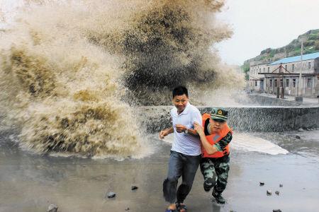 7月13日,浙江省温州市北麂边防派出所官兵紧急转移途经巨浪前的居民。新华社发