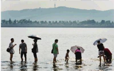 7月20日傍晚,湘江长沙杜甫江阁段,江水刚刚淹没亲水平台,一些市民在浅水区游泳玩耍。 记者 李丹 摄