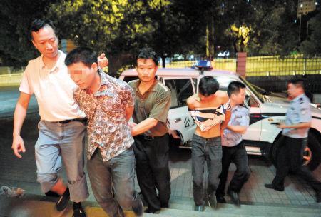 昨晚11时多,冯先明(左三)和邓国亮(左一)将抓获的两名砸车偷包的犯罪嫌疑人押回雨花区巡特警大队。石祯专摄