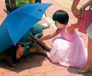 小女孩为倒地清洁工遮阳伞