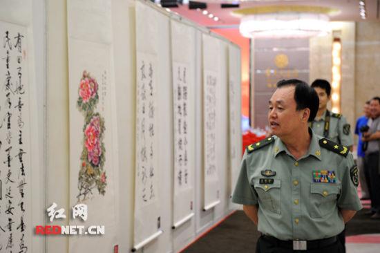 湖南省军区司令员黄跃进正在欣赏展出的书画作品。