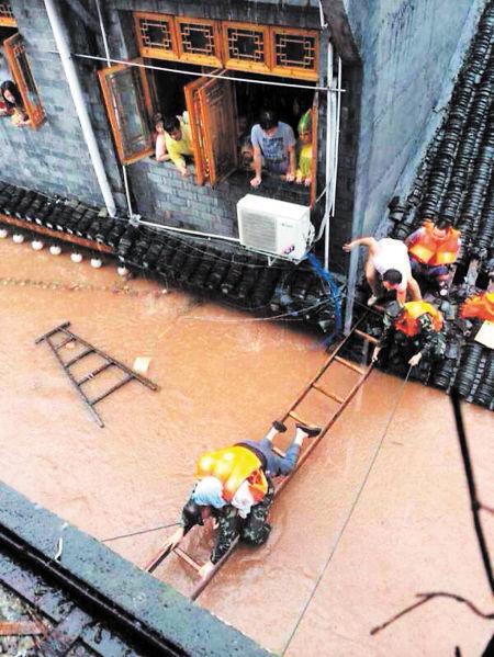 昨日,暴雨袭击凤凰,凤凰古城出现内涝,图为当地居民在救援人员的帮助下紧急转移。吴春柳 摄